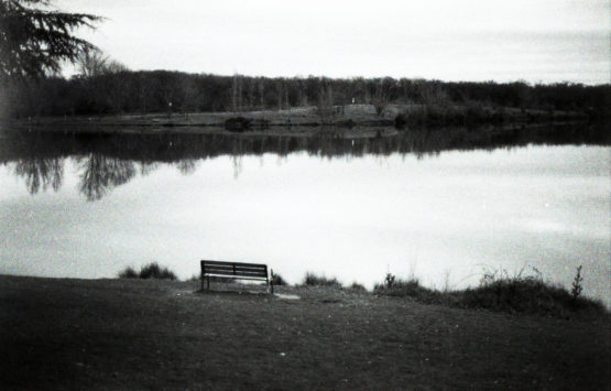 Photographie en noir et blanc d'un banc devant un lac